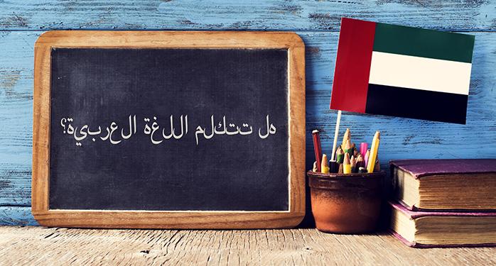 黒板に書かれたアラビア語の文章とUAEの国旗